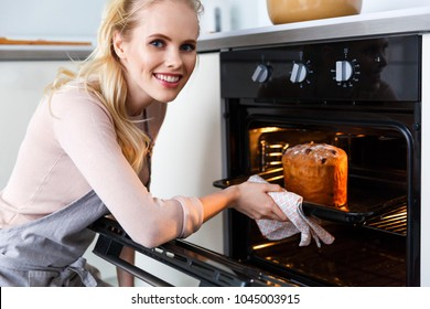 beautiful young woman in apron baking easter cake in oven and smiling at camera