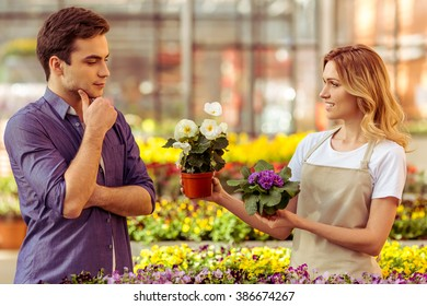 Beautiful young woman in apron is smiling while offering a plant to man in orangery