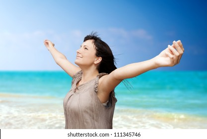 Beautiful young woman with arms raised standing on beach