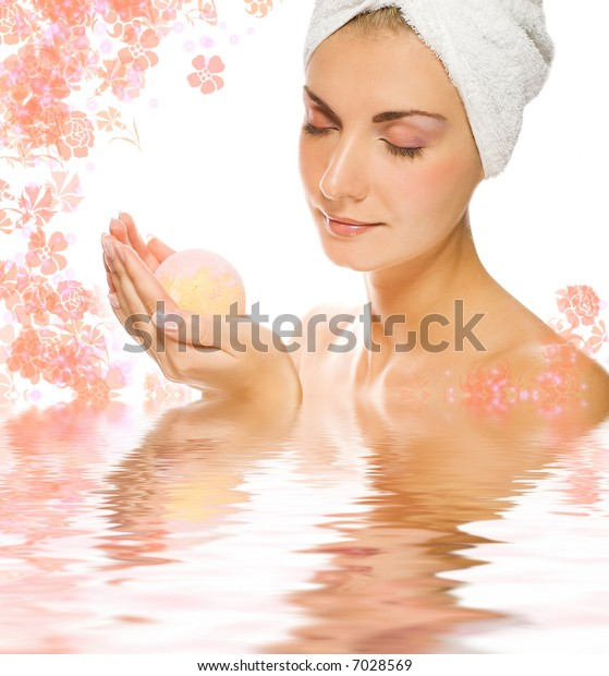 Beautiful young woman with aroma bath ball reflected in rendered water