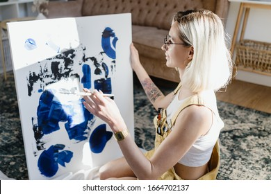 Beautiful young woman artist drawing in a comfy home interior