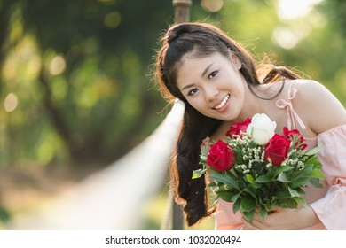 beautiful young woman asian girl pink dress happy smiling with flowers roses red and white valentines day in the garden picture style vintage