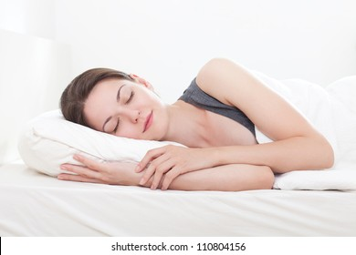 Beautiful young woman asleep, on white background