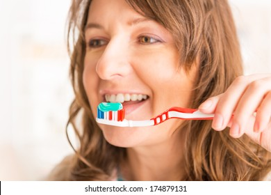 Beautiful young woman attempting to brush her teeth with toothbrush