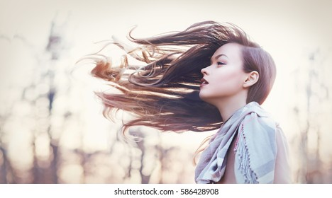 beautiful young woman autumn evening her hair tooked by the wind and fly before her Fashion toning