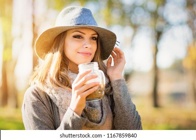 Beautiful young woman in autumn in park, smiling and drinking coffee. Female model in gray outfit with wide brim gray felt hat. Natural lighting, retouched.