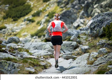 beautiful young woman with backpack running on the mountain stony trail