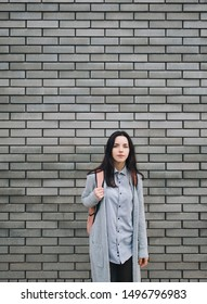 Beautiful young woman with a backpack standing half a turn near the gray brick wall. Lonely look. Pensive girl. Copy space.
