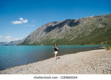beautiful young woman with backpack walking near Gjende lake, Besseggen ridge, Jotunheimen National Park, Norway