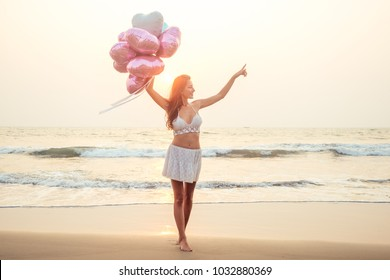 beautiful and young woman with balloons points to the sea