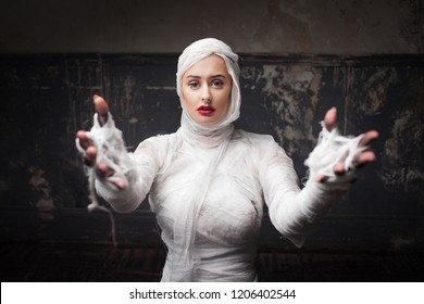 Beautiful young woman in bandages. Girl in a mummy costume. Halloween or plastic surgery concept