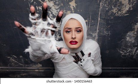 Beautiful young woman in bandages. Girl in a mummy costume, Pulling hand. Halloween or plastic surgery concept