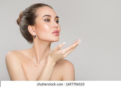 beautiful young woman with bare shoulders on a gray background. Skin and face care concept. spa