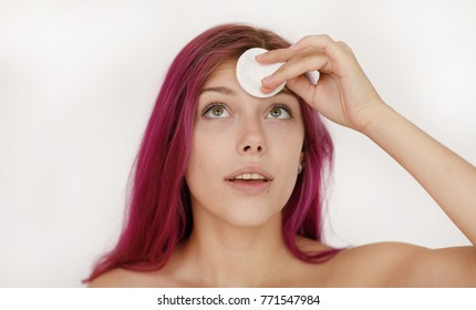 Beautiful young woman with bare shoulders and purple hair looking upwards brushing her forehead from makeup with a white cotton pad in a bright room.  Beauty procedures skin care concept.