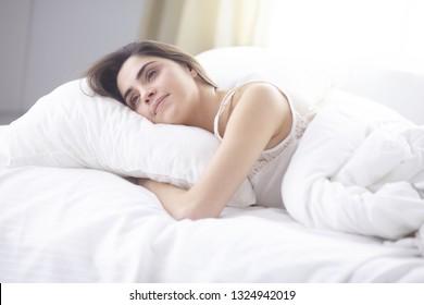 schöne junge Frau, die morgens im Bett liegt. Schönes Model-Gesicht sieht sexy in der Kamera aus