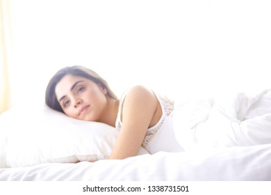 beautiful young woman basking in bed in the morning. Beautiful Model face looks sexy in camera