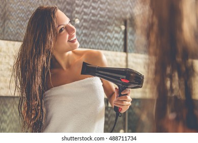 Beautiful young woman in bath towel is using a hair dryer and smiling while looking into the mirror in bathroom