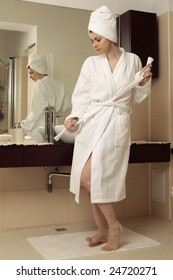 Beautiful young woman in bathrobe in front of the mirror