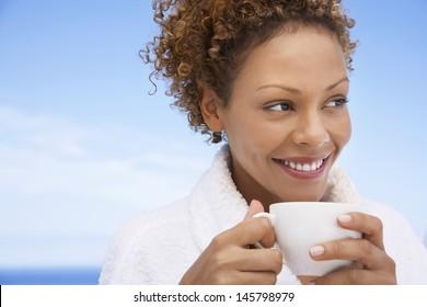 Beautiful young woman in bathrobe having coffee outdoors
