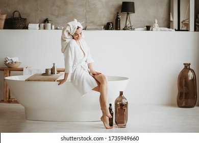 Beautiful young woman in bathrobe sitting on the edge of bathtub. Self care concept.