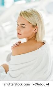 beautiful young woman in bathrobe touching her skin on shoulder