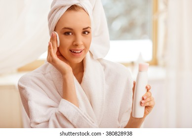 Beautiful young woman in a bathrobe with a towel on her head holding a bottle of toner and clearing her face with a sponge, looking at camera and smiling
