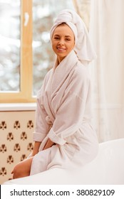 Beautiful young woman in a bathrobe with a towel on her head looking at camera and smiling while sitting in the bathroom