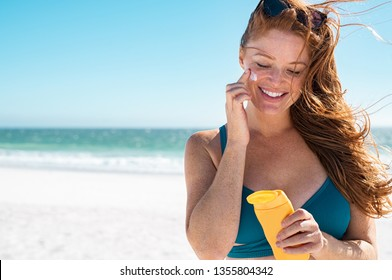Beautiful young woman at beach applying sunscreen on face. Mature woman with freckles and red hair enjoying summer holiday while applying suntan lotion. Portrait of smiling lady with healthy skin.