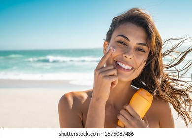 Beautiful young woman at beach applying sunscreen on face and looking at camera. Beauty latin girl applying suntan lotion at sea. Portrait of happy woman with healthy skin applying sunblock on cheek.