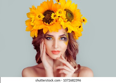 Beautiful young woman beauty and fashion portrait with wreath headband of sunflower yellow flowers painting on face looking at you isolated on light green background wall in studio horizontal shot.