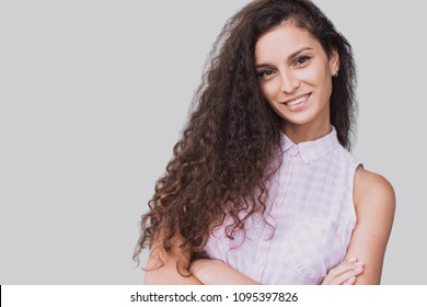 Beautiful young woman beauty portrait. Happy smiling girl with crossed hands looking at camera. Isolated on grey background.