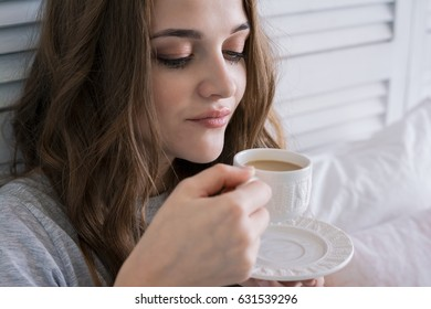 Beautiful young woman in bed in the bedroom drinking coffee in the morning