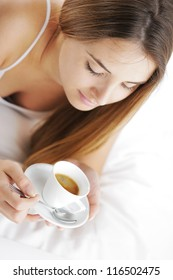 Beautiful young woman in bed drinking cofee in the morning.