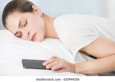 a beautiful young woman in bed, is pressing the snooze button in her phone
