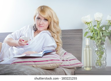 Beautiful young woman in bedroom wearing white men shirt, writing notes in notebook