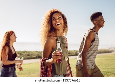 Beautiful young woman with beer walking with friends outdoors on a summer day. Female hanging out with friends outdoors.