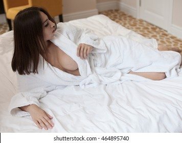 Beautiful young woman with big boobs in white bathrobe in bedroom at home