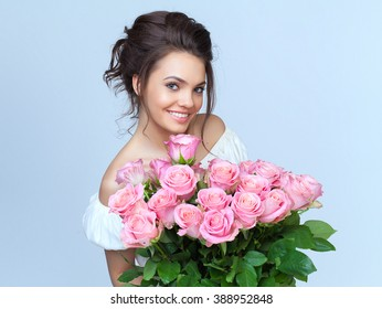 beautiful young woman with a big bouquet of roses flowers in a white dress on a light background