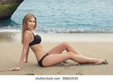 Beautiful young woman in bikini lying on sand near water. Outdoor shot. Tenerife.