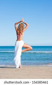 Beautiful young woman in bikini relaxing on the beach