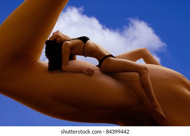 Beautiful young woman in bikini resting on a man's biceps. Fitness, tanning, health and beauty concept.