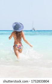 Beautiful young woman in bikini running into the ocean