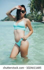 beautiful young woman in bikini and sunglasses at tropical sea resort