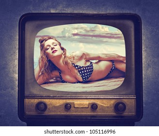 Beautiful young woman in bikini at the tv
