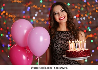Beautiful young woman with birthday cake and balloons against defocused lights