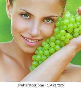 Beautiful young woman bites off from grape bunches, against summer green park.