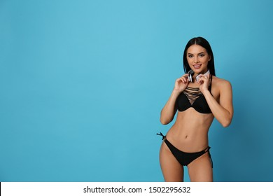 Beautiful young woman in black bikini with headphones on light blue background. Space for text