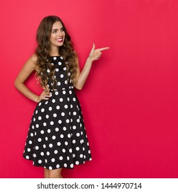Beautiful young woman in black cocktail dress in polka dots pattern is looking away, smiling and pointing. Three quarter length studio shot on red background.