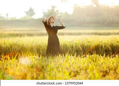 Beautiful young woman in black dress and straw hat. Girl enjoying the sun and nature in Asian green rice field. Canggu, Bali, Indonesia.