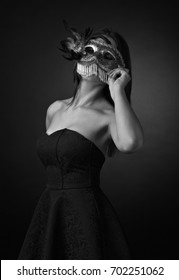 Beautiful young woman in black dress with carnival mask